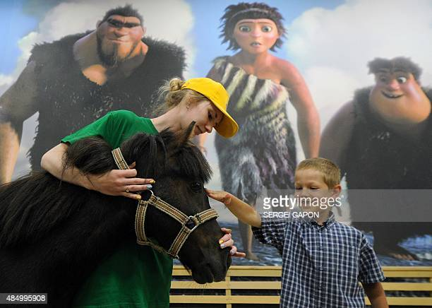 A boy strokes a pony at a petting zoo in Minsk on August 23 2015 AFP PHOTO / SERGEI GAPON