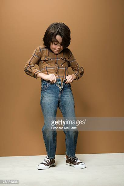 Boy (8-9) struggling to fasten jeans button