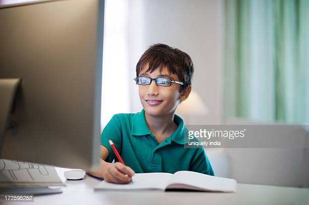 Boy studying in front of a desktop pc
