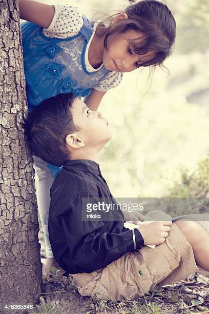 Boy studying outdoor his sister looking to him