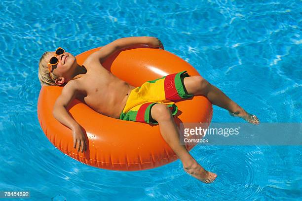 Boy sunbathing on inner tube in swimming pool