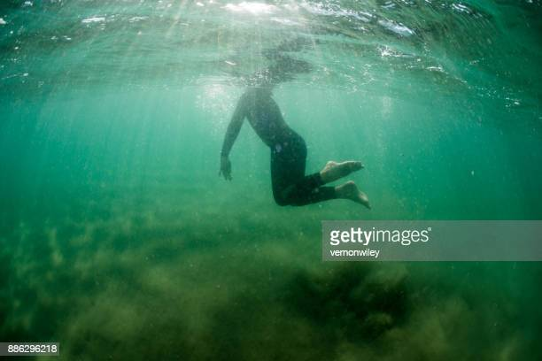 Boy surfacing and breathing while in the ocean