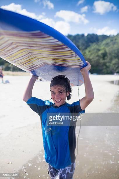 Boy surfer carrying surfboard