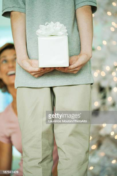Boy surprising his mother with a Christmas gift, cropped
