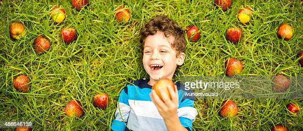 Boy surrounded by apples