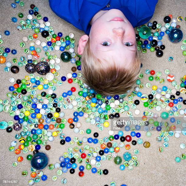 Boy Surrounded by Marbles