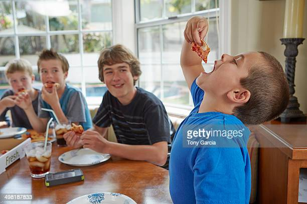 Boy swallowing pizza with mouth open