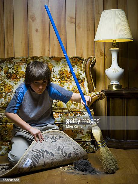 Boy sweeping dirt under rug