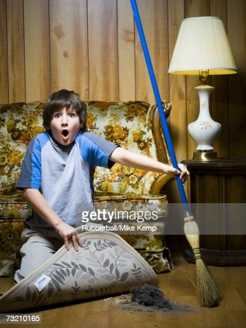 Boy Sweeping Dirt Under Rug Stock Photo Getty Images