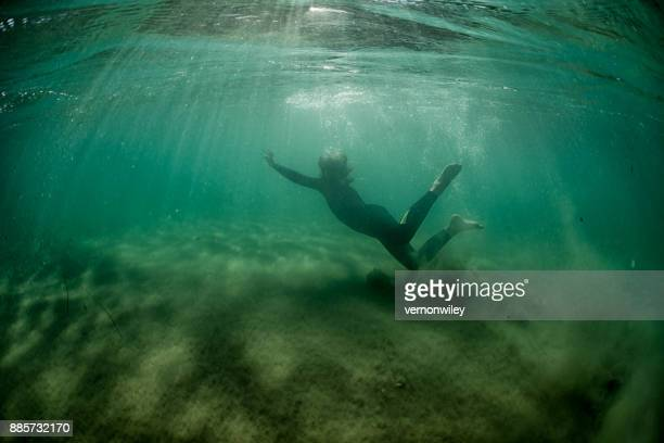 Boy swimming alone in the dark waters of the ocean