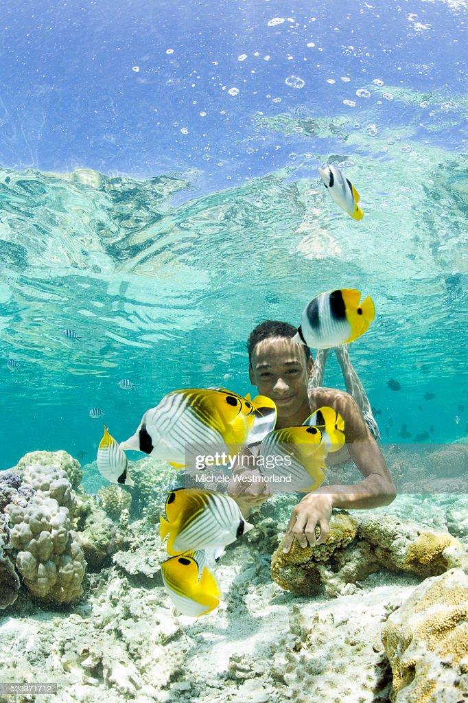 Boy Swimming Among Tropical Fish in Bora-Bora Lagoon