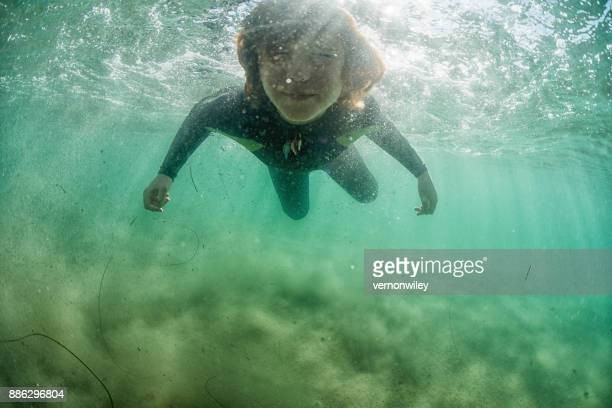 Boy swimming on the surface of the ocean
