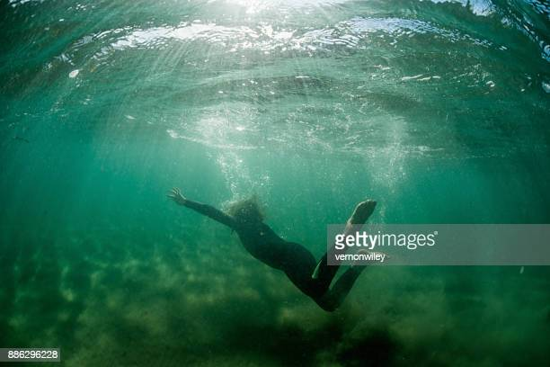 Boy swimming towards the surface of the waters all alone