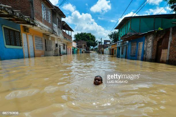 A boy swims in a flooded area of Cali Colombia on May 13 2017 after heavy rains caused the overflowing of the Cauca river Flooding and mudslides in...