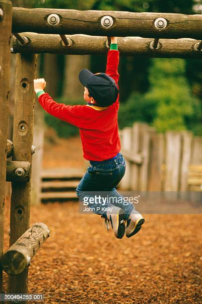 Boy (5-7) swinging from monkey bars in playground, rear view