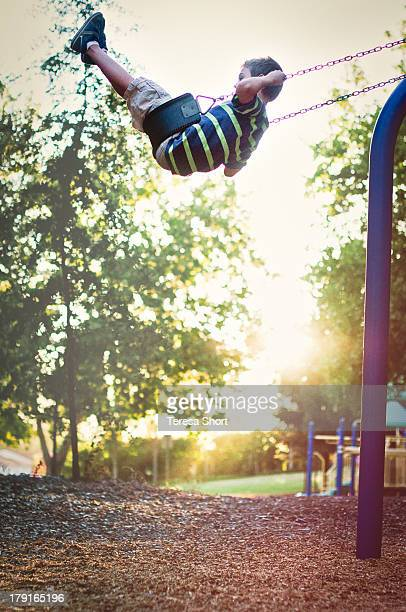 Boy Swinging High on Swing