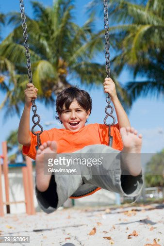 Boy swinging on a swing : Foto de stock