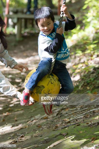 Boy Swinging On Rope Swing At Park