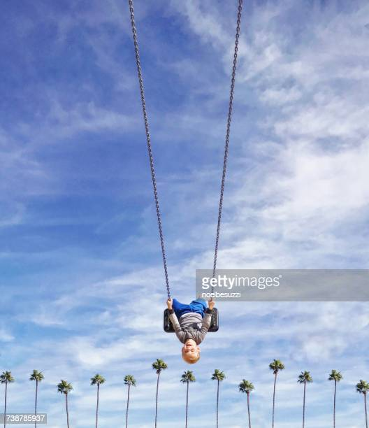 Boy swinging upside down on a swing over a row of palm trees, Orange County, California, America, USA