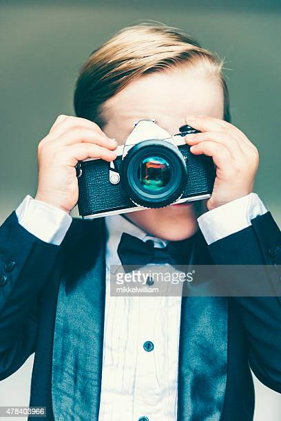Boy takes a photo using an old retro camera