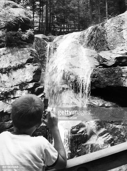 A boy takes a picture at the Flume Gorge a natural gorge extending 800 feet at the base of Mount Liberty in Franconia Notch State Park in Lincoln NH...