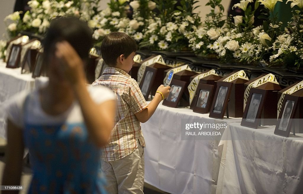 A boy takes a picture of the urn with the remains of his relative who was disappeared during the Colombian civil war until recently, on June 21, 2013 in Medellin, Antioquia department, Colombia. In a ceremony, relatives of 36 victims received the remains of their loved ones, which were recently found in common graves due to information given by demobilized combatants of both, leftist guerrillas and right-wing paramilitary groups, in the framework of the country's peace process. AFP PHOTO/Raul ARBOLEDA