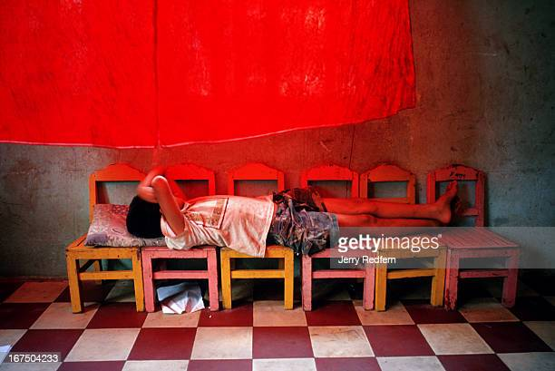 A boy takes an afternoon nap on a set of small chairs beneath a billowing red curtain in the Chea Sim Orphanage The curtain is lit by the...