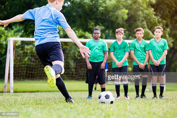 Boy takes penalty shot during soccer game