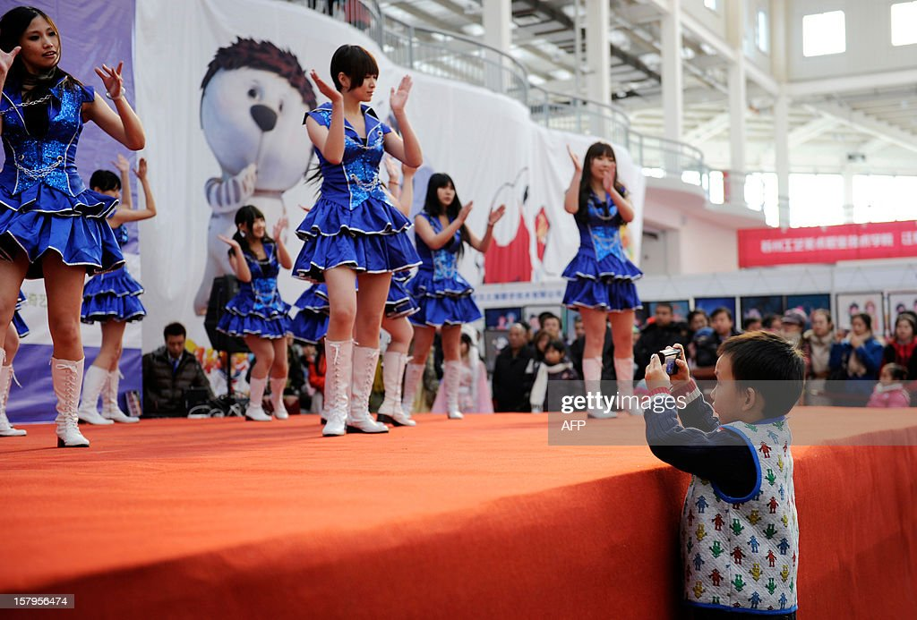 A boy (R) takes photos during a 'cosplay ' show at the International Anime Fair in Beijing on December 8, 2012. The fair is being held at the Beijing Crab Island International Convention and Exhibition Centre from December 1 to 9.