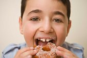 Boy taking bite of doughnut