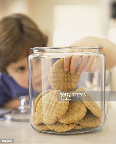 Boy taking cookie from jar