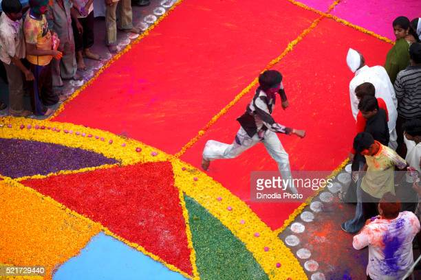 Boy taking leap near colourful flower Rangoli made on road for immersion celebration of Lord Ganesh, Sangli