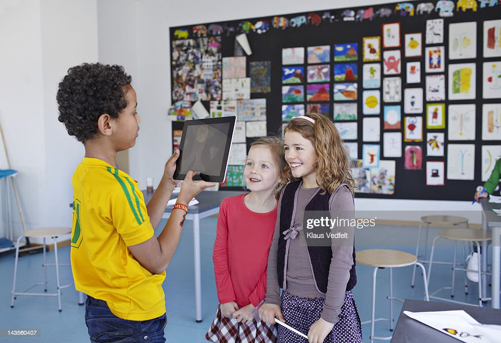 Boy taking photos with tablet of 2 classmates : Stock Photo