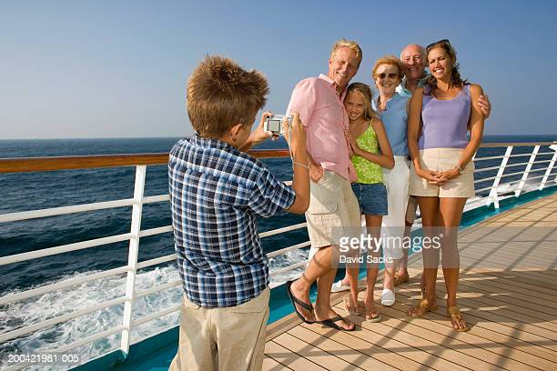 Boy (10-12) taking picture of family
