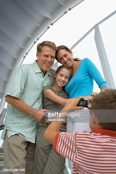 Boy (10-12) taking picture of family smiling