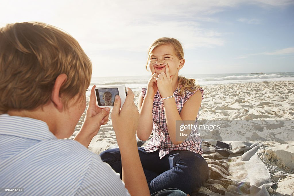 Boy taking picture of girl with smart phone : Stock Photo