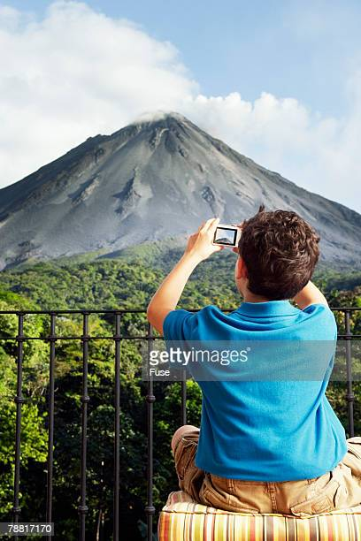 Boy Taking Picture of Mountain