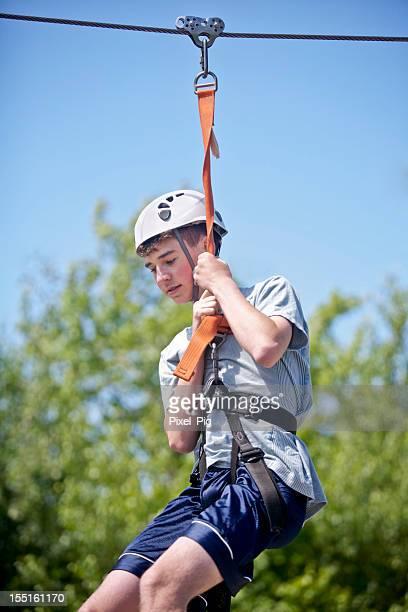 Petit garçon prenant une tyrolienne en descendant la montagne