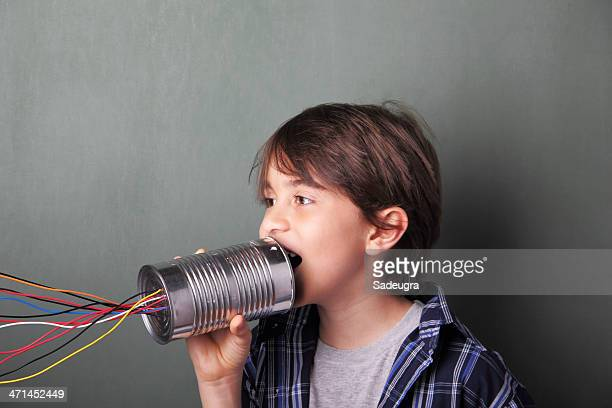 Boy talking into tin can with colored wires