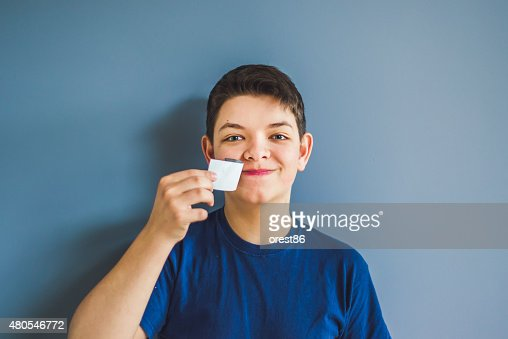 boy tears off an adhesive tape from a mouth : Stock Photo
