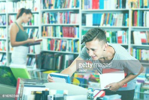 Boy teenager choosing new book in shop : Stock Photo