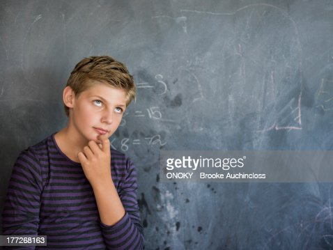 Boy thinking in front of a blackboard in a classroom
