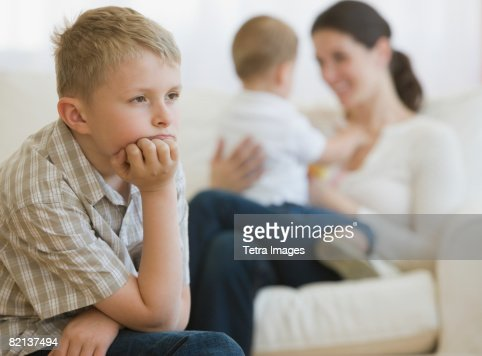 Boy thinking in front of mother and baby : Foto de stock