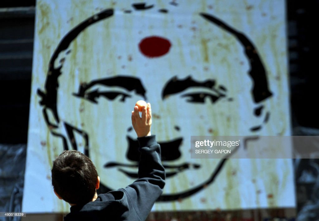 A boy thows an egg at an image of Russian President Vladimir Putin depicted as late German Nazi dictator Adolf Hitler during a flash mob event in the center of Kiev on May 24, 2014, a day before the presidential elction in Ukraine. Ukraine was counting down today to a presidential election seen as crucial to its very survival after months of turmoil that has driven the country to the brink of civil war.