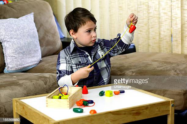 Boy threading a string of beads