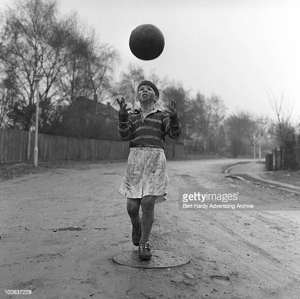 A boy throwing a ball into the air after a muddy game of football 3rd February 1962