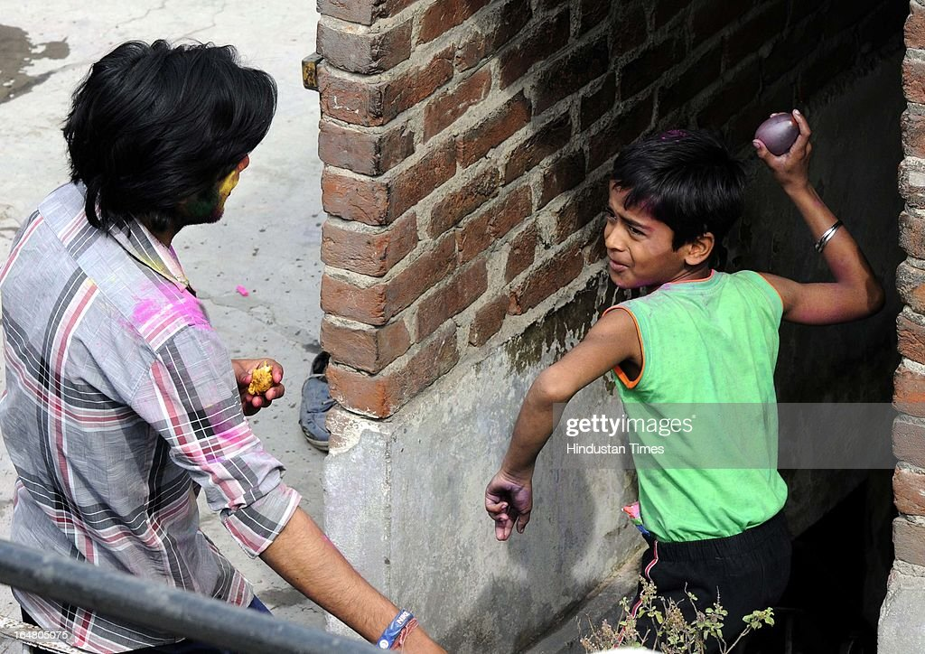 A boy throwing a water balloon during Holi festival celebration on March 27, 2013 in New Delhi, India. Holi, festival of color is Hindu religious festival also called Basantotsav or spring festival as it mark the arrival of spring. People gather together to play colors, sing and dance to traditional tunes and eat sweets specially Gujiyas.