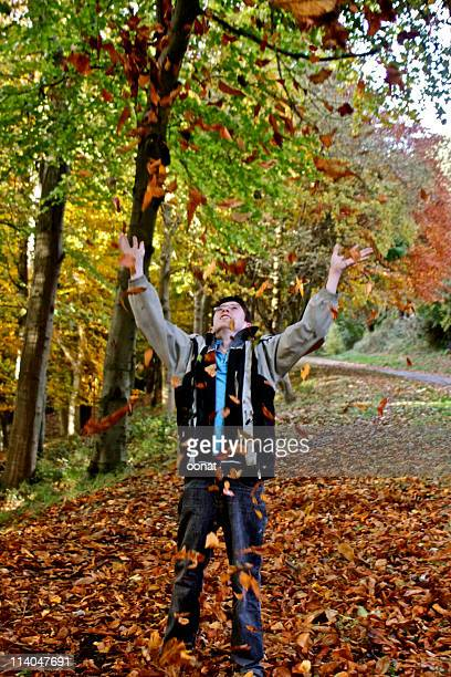Boy throwing autumn leaves