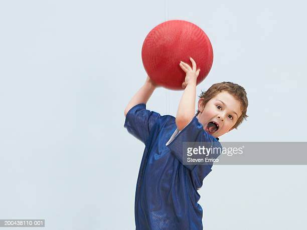 Boy (5-7) throwing ball, mouth open (blurred motion)
