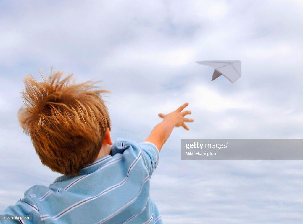 Boy (4-6) throwing paper aeroplane, outdoors, rear view